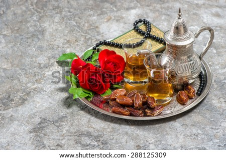 Tea, dates fruits, red rose flower, holy book quran and rosary. Islamic holidays decoration. Ramadan kareem. Eid mubarak. Oriental hospitality concept. Vintage style toned picture - stock photo
