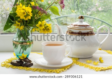 Tea drinking in the morning near the window: a cup of tea, pieces of chocolate, kettle and bouquet of flowers in a vase. Seen through the glass visible of green plants. Selective focus  - stock photo