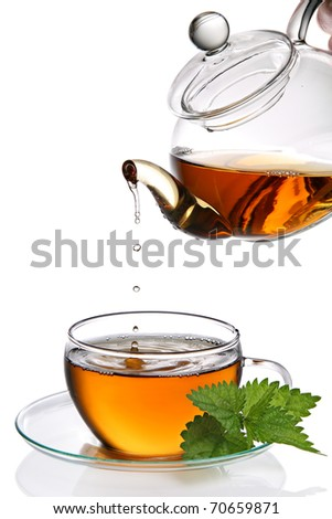 Tea dripping into glass tea cup (clipping path included) - stock photo