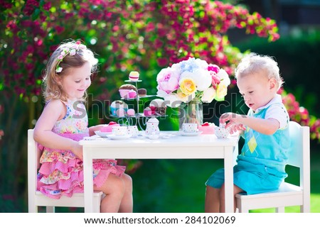 Tea garden party for kids. Child birthday celebration. Little boy and girl play outdoor drinking hot chocolate and eating cake. Children eat sweets. Kid event with toy dish and flower decoration. - stock photo