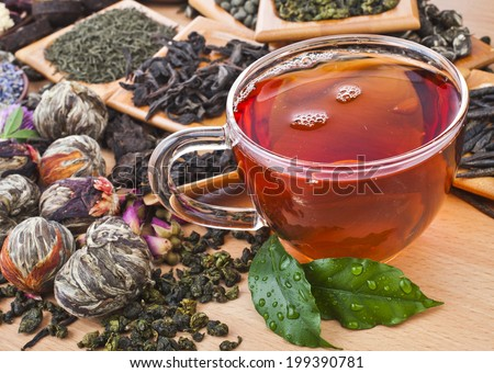 Tea glass cup and collection of different dry types tea (green,black, herbal) on kitchen wooden table background - stock photo