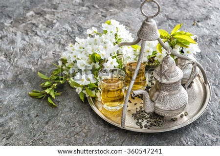 Tea glasses and pot. Oriental table decoration with flowers - stock photo