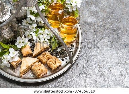 Tea glasses and pot, traditional sweets. Islamic holidays decoration - stock photo
