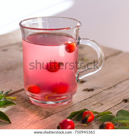 Tea herbal drink from rose hips in glass cup on wooden background