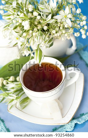 tea in a cup of white flowers and lilies of the valley - stock photo