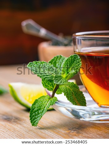 Tea in a glass cup, mint leaves, dried tea, sliced lime, cane brown sugar - stock photo