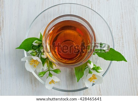 Tea in a glass cup with jasmine flowers, top view