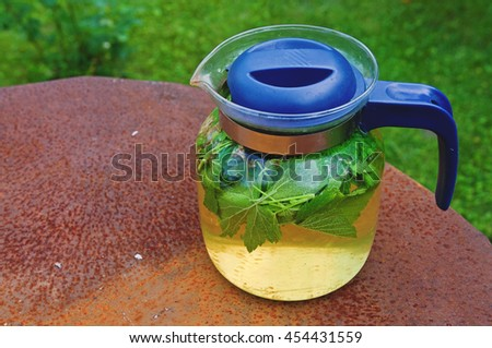 Tea in a glass teapot with leaves of black currant and green leaf on a background of rusty sheet metal - stock photo