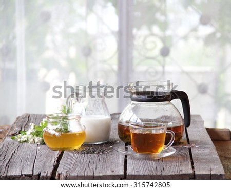Tea in a transparent cup submitted with honey and milk