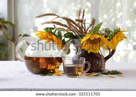 Tea in a transparent teapot and a bouquet of sunflowers