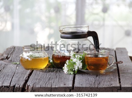 Tea in a transparent teapot submitted with honey