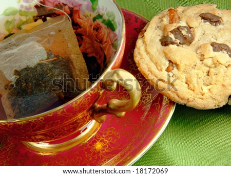 Tea in and antique cup with a chocolate chip cookie. - stock photo