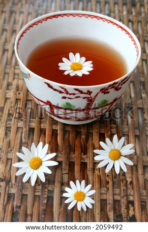 Tea in antique Chinese bowl with daisy flowers