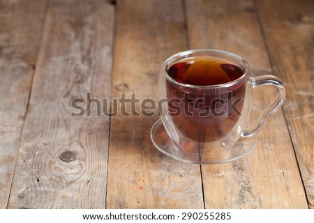 Tea in glass cup on wooden table background.  - stock photo