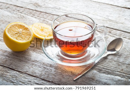 Tea in glass cup on wooden table background.
