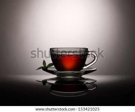 tea in glass cup  with fresh  leafs of mint on dark grey background - stock photo