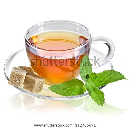tea in glass cup with mint leaf and brown cane sugar cubes isolated on a white background - stock photo