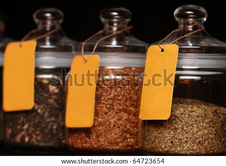 Tea in glass jars on black background - stock photo