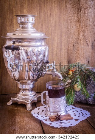 Tea in glass with coaster  and russian samovar on wooden background. Cinnamon and anise star with white doily. Home christmas decoration - stock photo