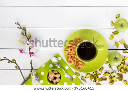 tea in green cup,  orchid flower, pretzels,  ripe green apples, green dry decor, cane sugar in green baby bucket, green napkin at white polka dots on white painted wooden table, top view - stock photo