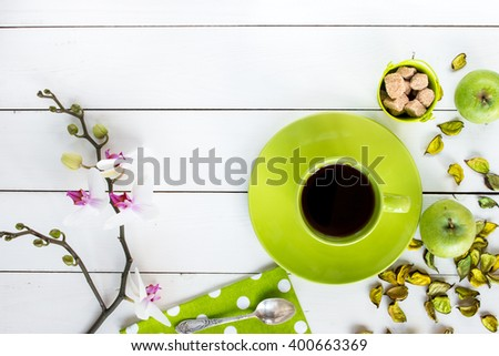 tea in green cup,  orchid flower, ripe green apples, green dry decor, cane sugar in green baby bucket, green napkin at white polka dots on white painted wooden table, top view - stock photo