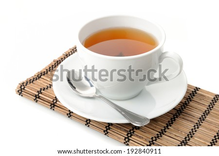 tea in white cup on bamboo mat - stock photo