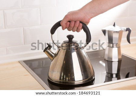 Tea kettle in hand on black stove. Close up - stock photo