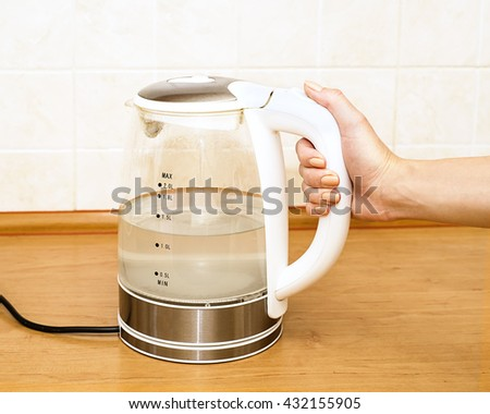 Tea kettle with boiling water in the kitchen close up,  Woman hand hold the glass electric kettle, preparing hot drink - stock photo