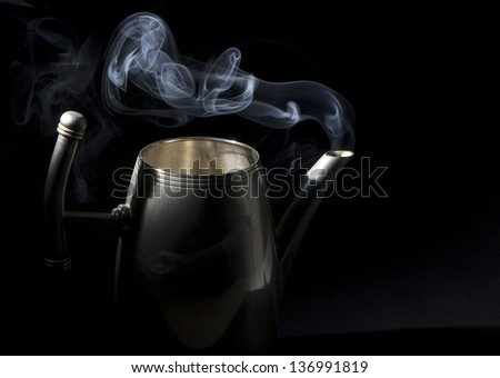 Tea kettle with boiling water on black background - stock photo