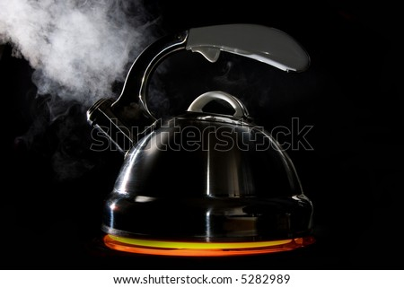Tea kettle with boiling water on black background. Heater glow below the kettle. - stock photo