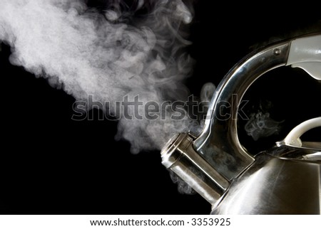 Tea kettle with boiling water; steam against a black background. - stock photo