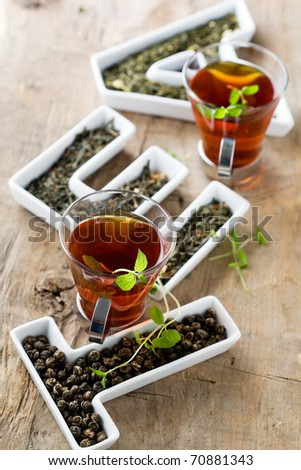 Tea leaves in letters and two cups of tea - stock photo
