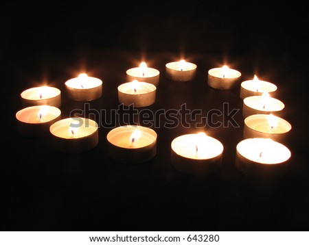 Tea light candles arranged in a heart shape - stock photo