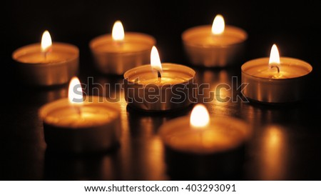 Tea light candles on a black background.