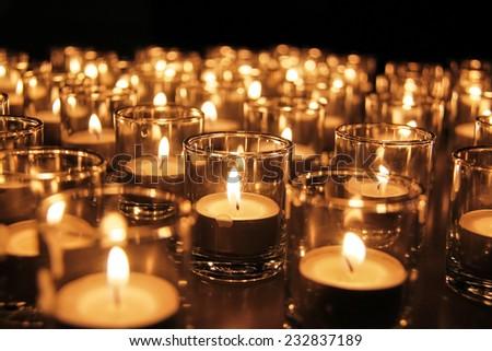 Tea lights in glass jar illuminates a dark surrounding - stock photo