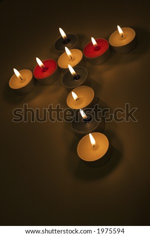Tea lights in shape of Christian cross in seasonal Christmas colours - stock photo