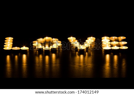 "tea lights in the shape of a word ""love"" on wood foreground - stock photo"
