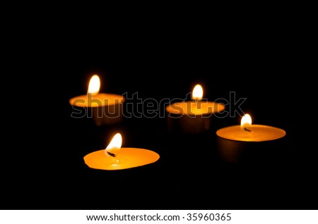 Tea Lights on a black background with shallow depth of field - stock photo