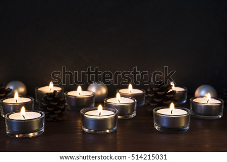 Tea lights with pine cones and baubles on a wooden surface, with copy space.