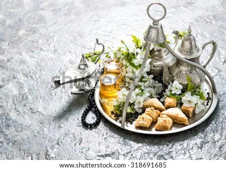 Tea pot and glasses, sweets, traditional oriental delight baklava. Hari Raya Aidilfitri - stock photo