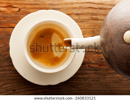 tea pour cup pot wooden table cafe top view - stock photo
