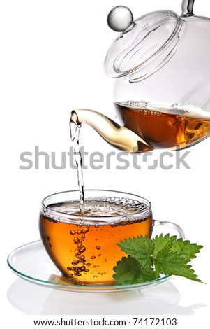Tea poured into cup on white background - stock photo