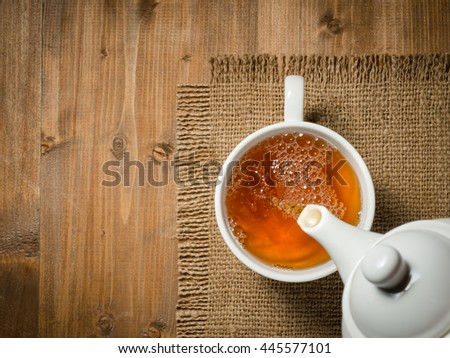 Tea pouring into cup on the old wooden background - stock photo