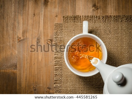 Tea pouring into cup on the old wooden background
