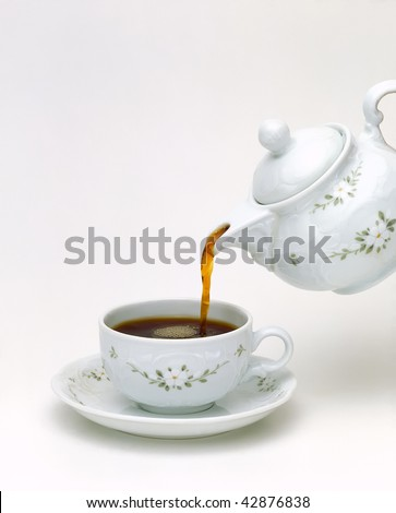 Tea pouring into glass cup isolated on white background - stock photo