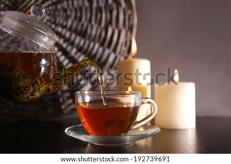 Tea pouring into glass cup on dark background - stock photo