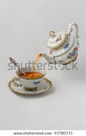 Tea pours into a cup with lemon from teapot - stock photo