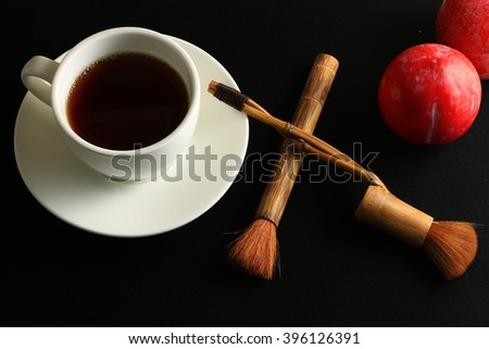 Tea, red fruits and black background.