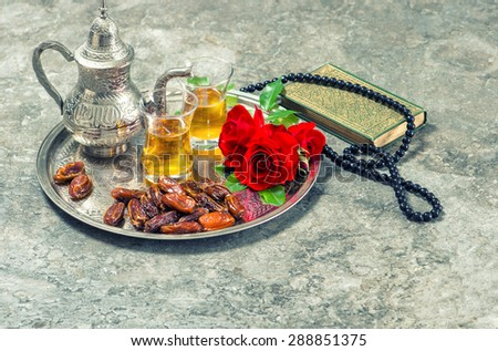 Tea, red rose flower, dates, holy book quran and rosary. Islamic holidays decoration. Ramadan kareem. Eid mubarak. Oriental hospitality concept. Retro style toned picture - stock photo