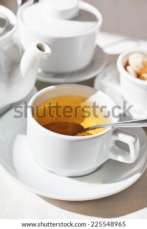 tea set and white porcelain cup with herbal tea